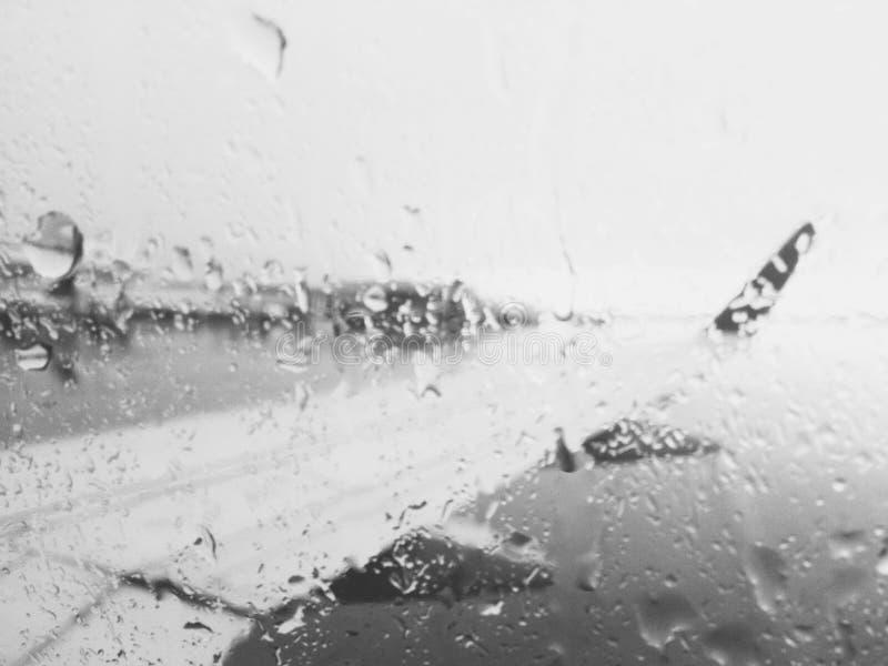 Airplane wing through rainy window royalty free stock photography