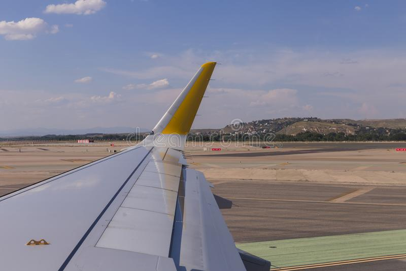 Airplane wing on the runway at airport on a sunny day. Travel and holidays concept. view from the passengers window. Road, transportation, takeoff, flying royalty free stock images