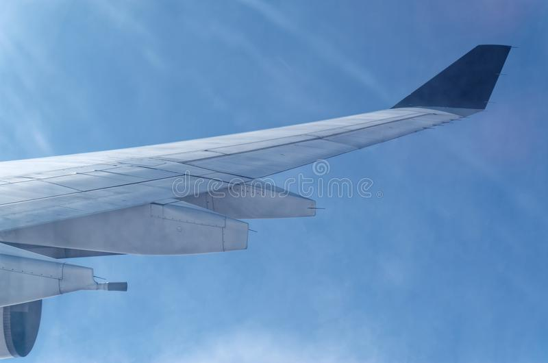 Airplane wing and sunbeams on the blue sky. Looking on an a part of the airplane wing in the air and sunbeams in the blue sky stock image