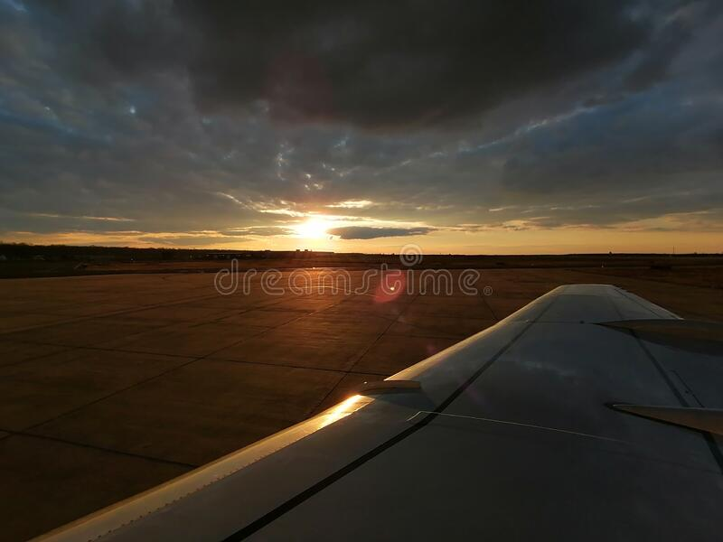On airplane wing in sunset royalty free stock image