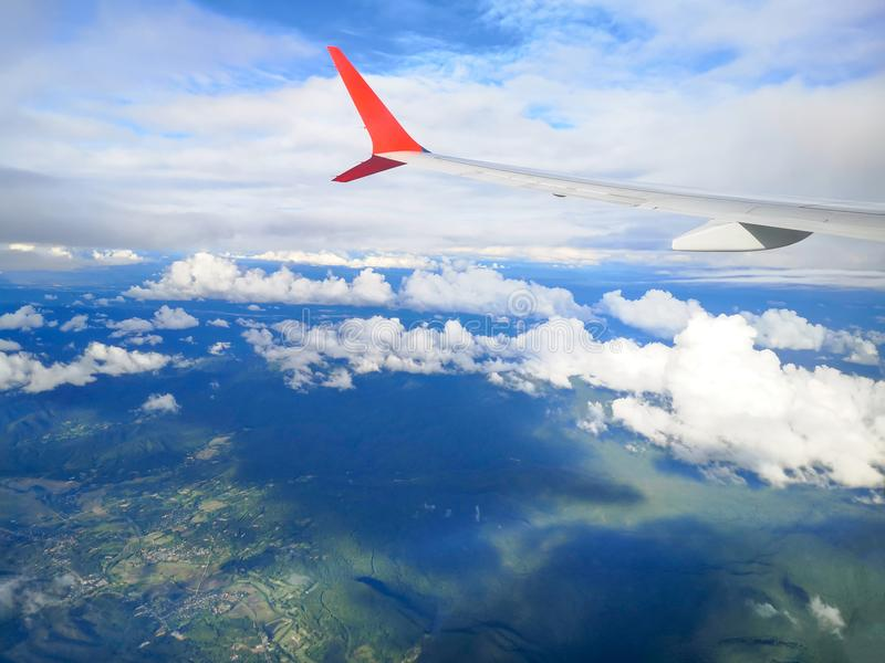 Airplane wing view with a cloud background,mountain and city. royalty free stock photography