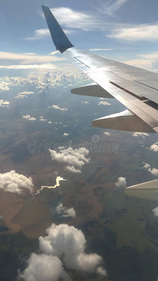 Airplane wing view out of the window on the cloudy sky background. Holiday vacation background. Wing of airplane flying above the royalty free stock photo
