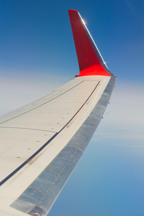 Airplane wings. In the blue clouds stock photo