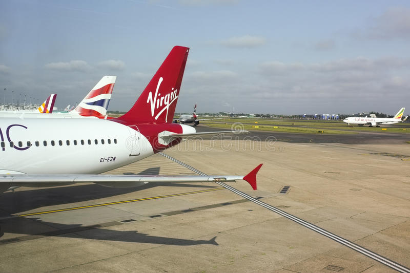 Airplanes at Heathrow Airport. Virgin and tails of other airline airplanes parked on the runway at Heathrow Airport in London stock images