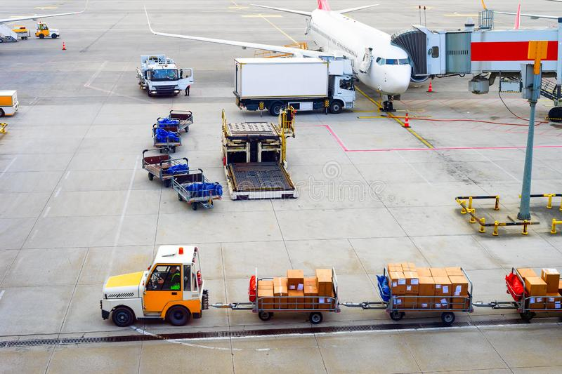 Airplanes, parcels, luggage carrier, airport. Airplanes, gangway, truck, parcels carrier, luggage carts at airport runway, aerial view royalty free stock photography