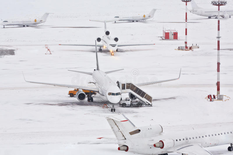 Airplanes and serving machinery. On snowy airfield royalty free stock photography