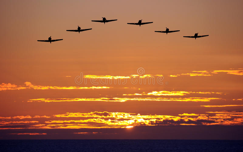 Airplanes at sunset. Formation of propeller airplanes over the sea at sunset stock images