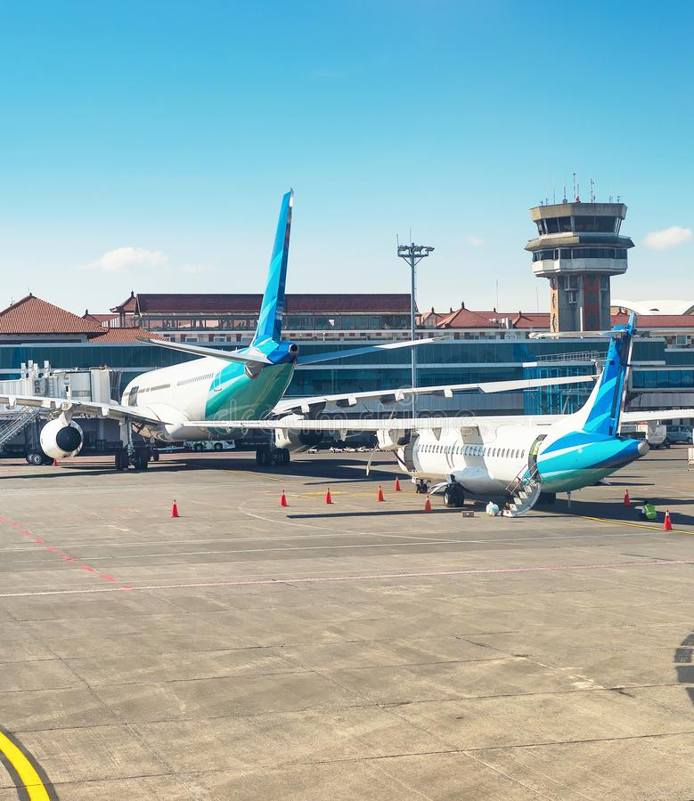 Airplanes and truck at runway in morning sunlight, Denpasar airport building, Bali, Indonesia. Airplanes and truck at runway in morning sunlight, Denpasar royalty free stock image