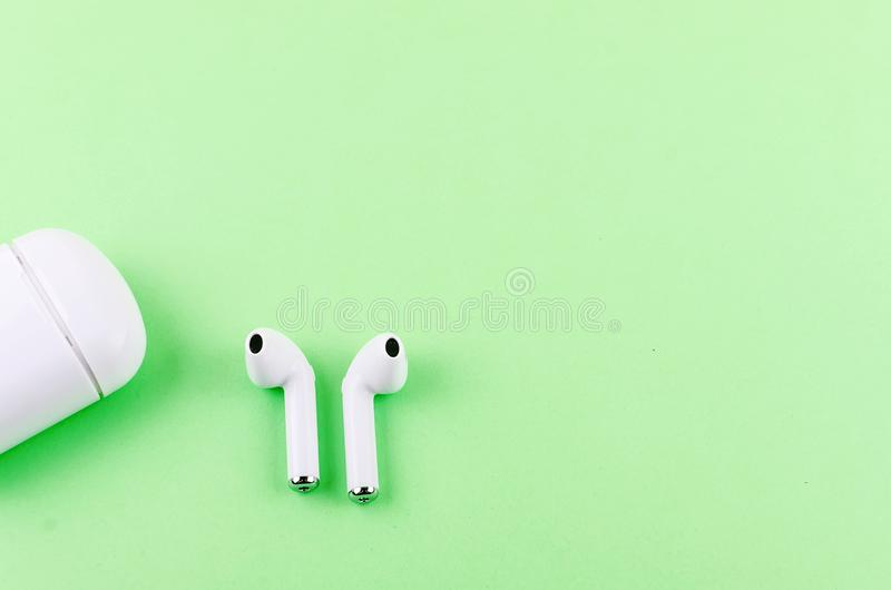 Airpods wireless headphones. New AirPods wireless Bluetooth entangled 3.5 headphones into the open charging case for Airpods for smartphone and a green stock image
