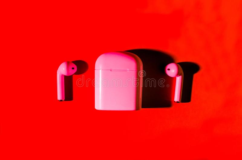 Airpods wireless headphones. New AirPods wireless Bluetooth entangled 3.5 headphones into the open charging case for smartphone in trendy neon red light on green stock photo