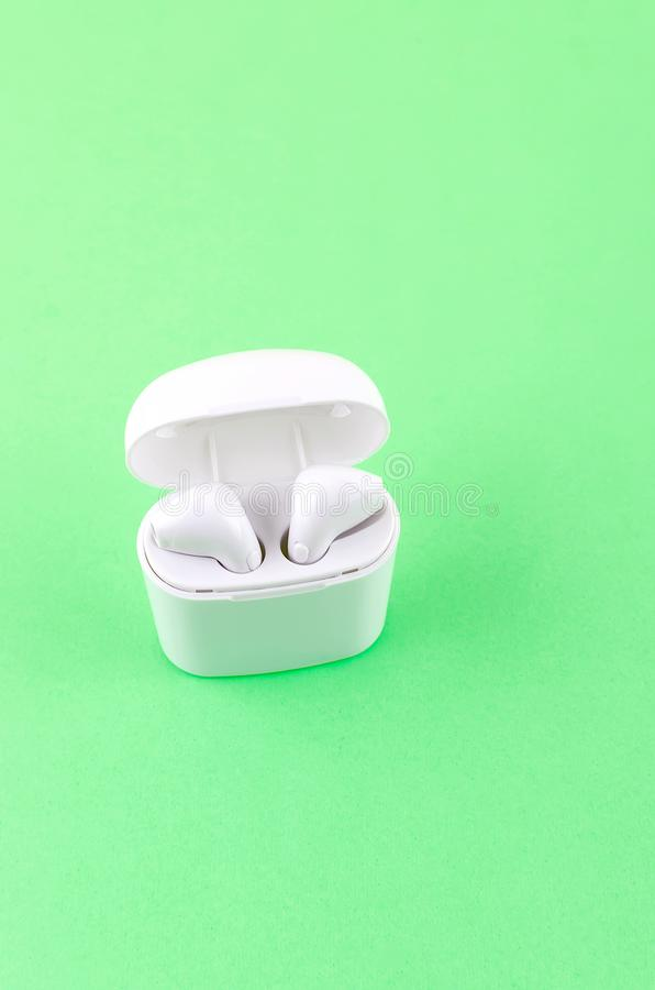 Airpods wireless headphones in an open case. New AirPods wireless Bluetooth entangled 3.5 headphones into the open charging case for Airpods for smartphone and a royalty free stock photography