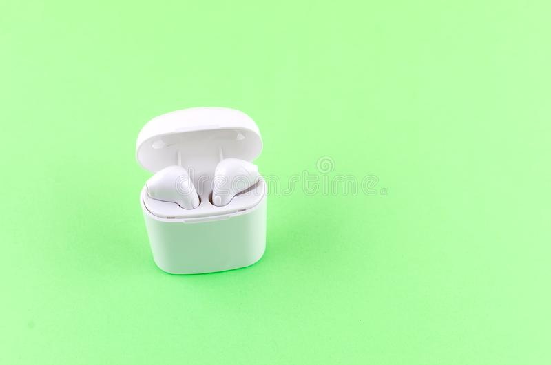 Airpods wireless headphones in an open case. New AirPods wireless Bluetooth entangled 3.5 headphones into the open charging case for Airpods for smartphone an a stock photography