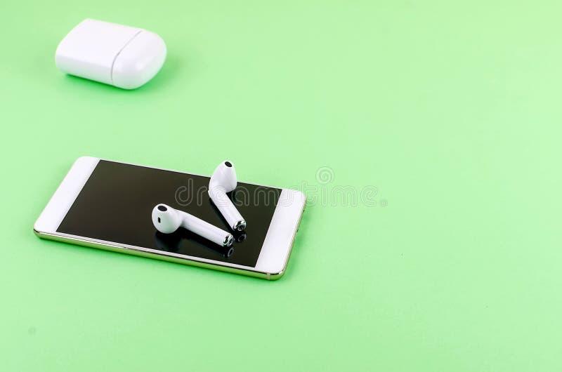 Airpods wireless headphones with phone. New AirPods wireless Bluetooth entangled 3.5 headphones iwith smartphone for Airpods for smartphone and a green stock photos
