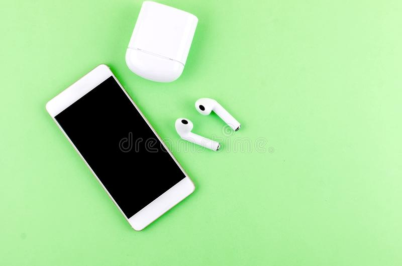 Airpods wireless headphones with phone. New AirPods wireless Bluetooth entangled 3.5 headphones iwith smartphone for Airpods for smartphone and a green stock photography