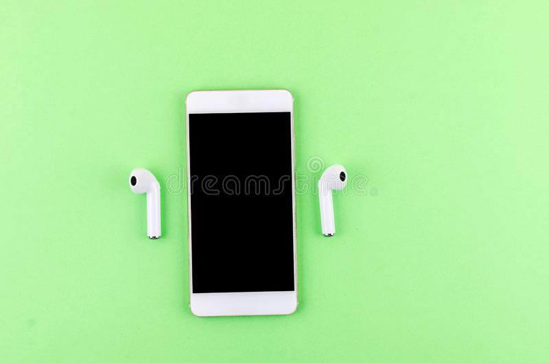 Airpods wireless headphones with phone. New AirPods wireless Bluetooth entangled 3.5 headphones iwith smartphone for Airpods for smartphone and a green royalty free stock photos