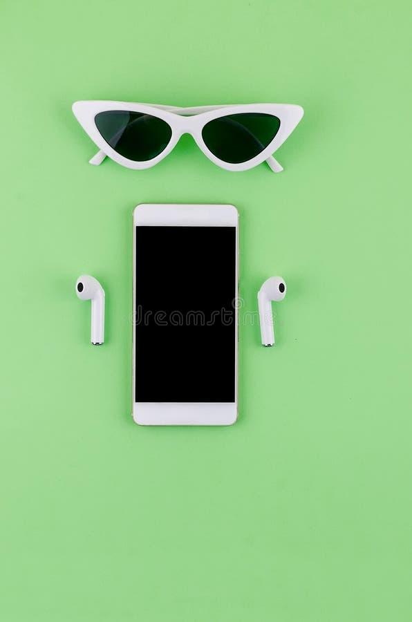 Airpods wireless headphones with phone. New AirPods wireless Bluetooth entangled 3.5 headphones iwith smartphone for Airpods for smartphone and a green stock photo