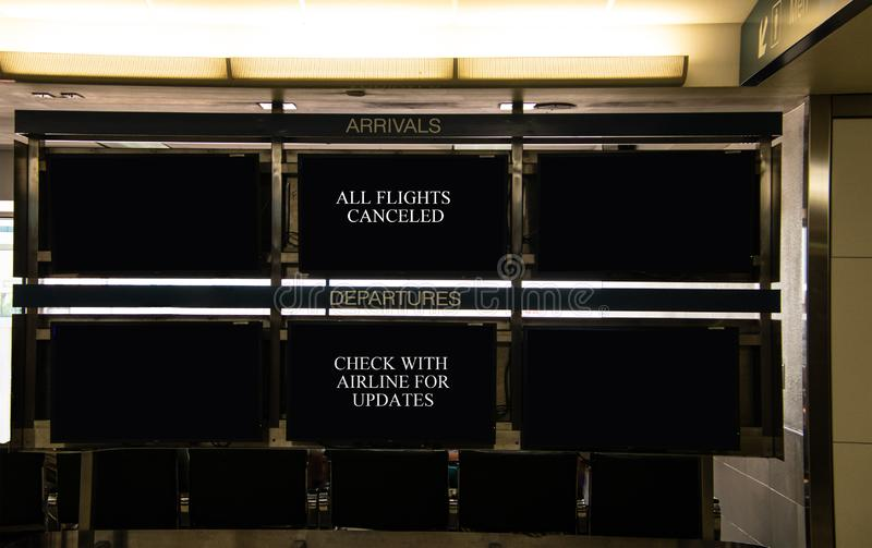 Airport arrivals and departure signs that indicate that all flights are canceled and that travelers should check with airlines. stock photography