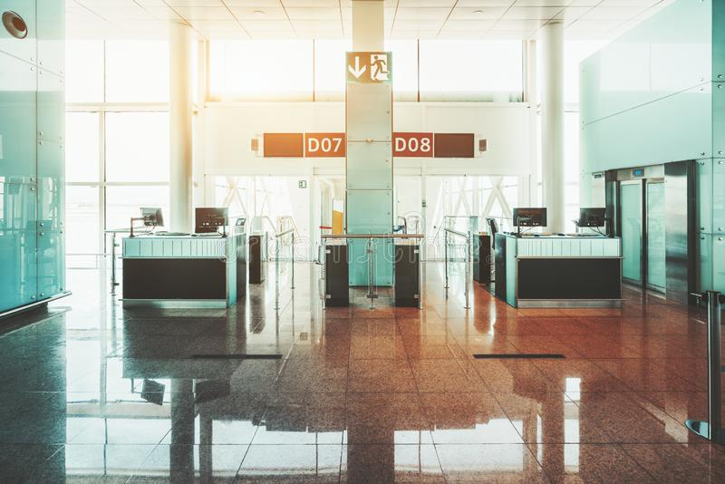 Airport boarding gates interior. Wide-angle view of empty gates of a modern airport terminal with computer monitors on the counter desks, information screens on stock image