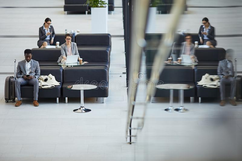 Airport business class lounge. Serious multi-ethnic business people sitting on sofas and using modern devices while waiting for boarding in airport business royalty free stock photography