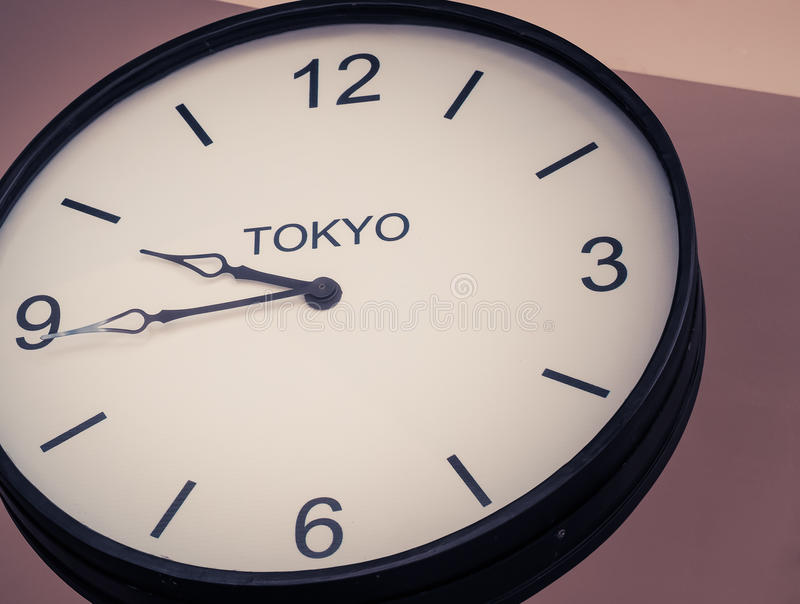 An airport clock showing Tokyo time zone. At 9 past 45, Retro filter color, Close up image royalty free stock photos