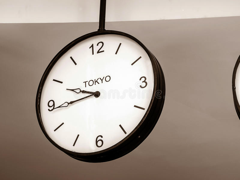 An airport clock showing Tokyo time zone. At 9 past 45, Retro filter color, Close up image stock photo
