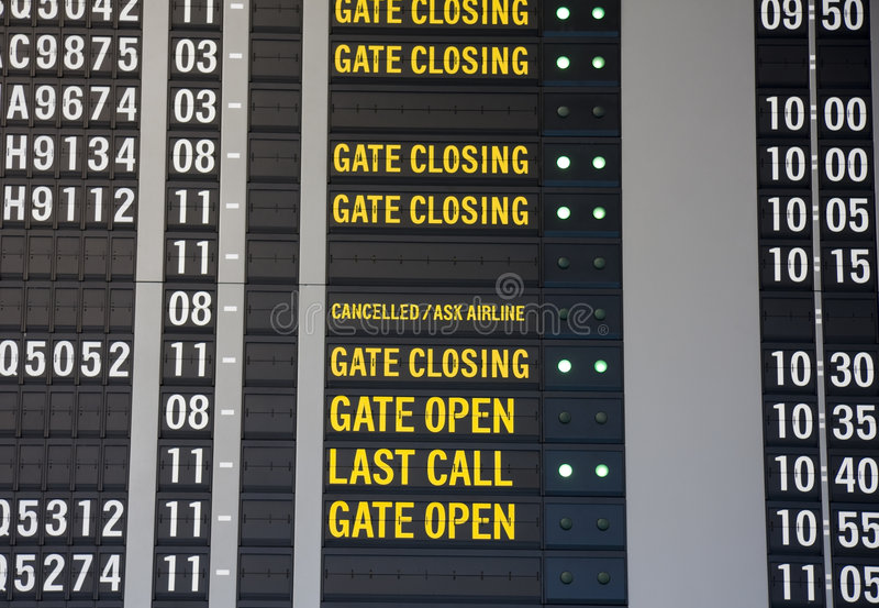 Airport Departure Board. Different status messages displayed on a flight departure board stock image