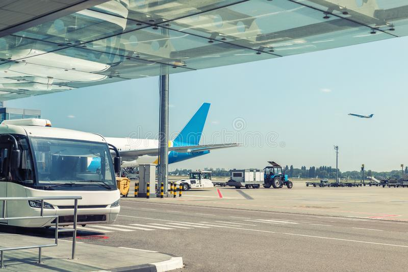 Airport environment and services. Shuttle bus waiting for passengers at terminal building. Big commercial plane on airfield. royalty free stock photos
