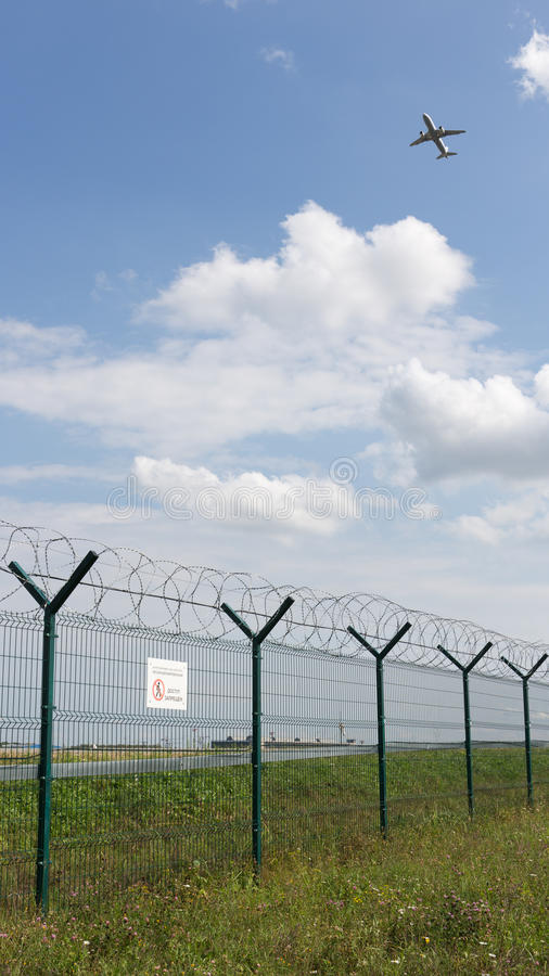 Airport fence, and the plane flies stock images