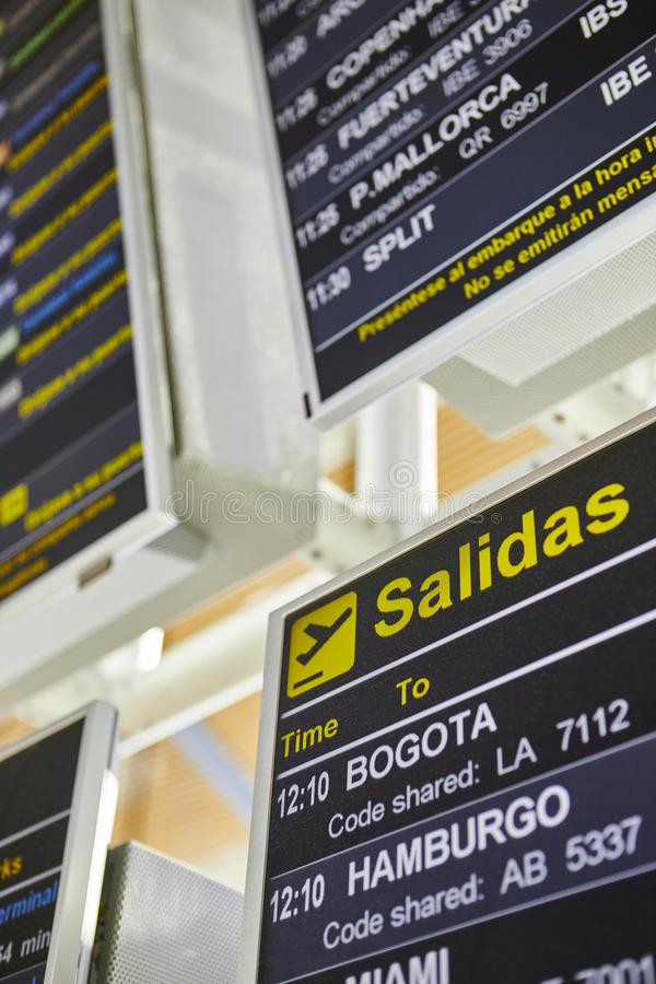 Airport flight departures info display on spanish language. Vertical stock image