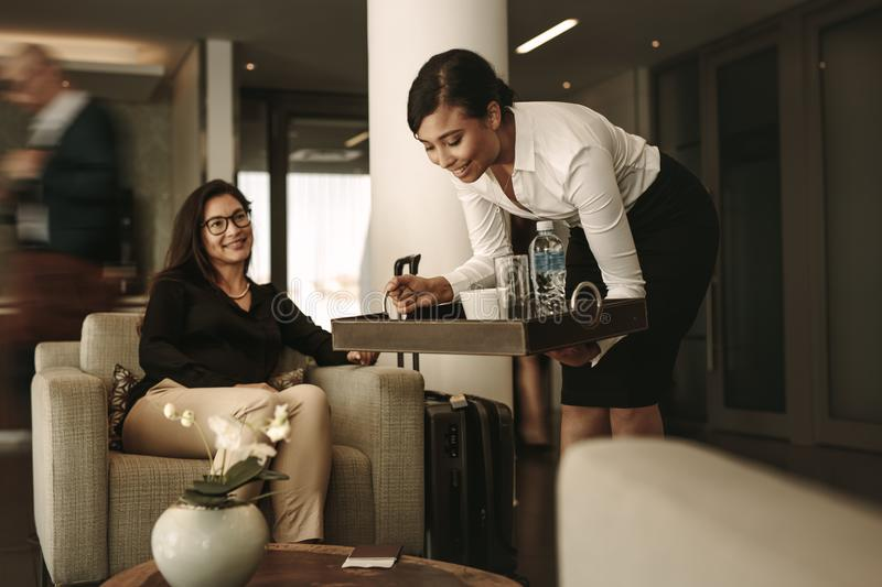 Airport lounge waitress serving coffee to female passenger stock image