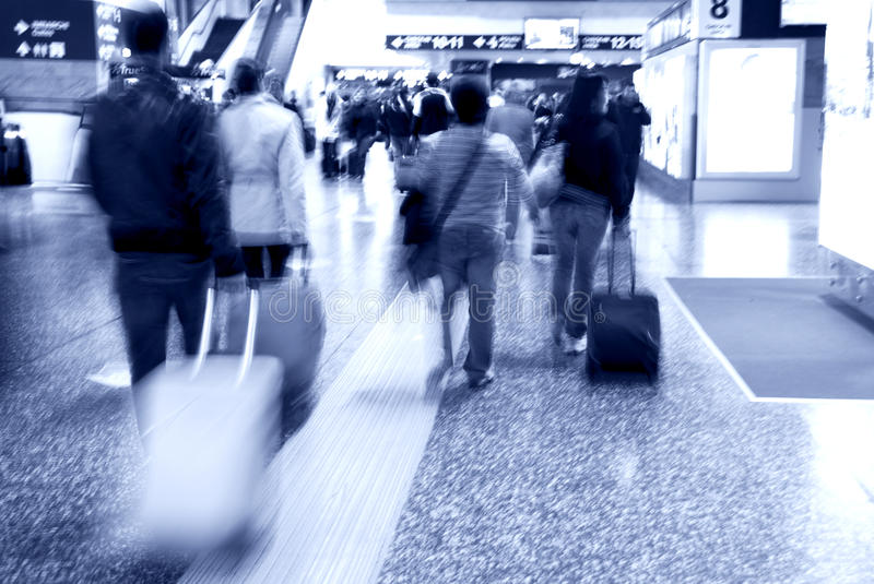 Airport movement. Abstract crowd in a rush hour in the airport - tourists and workers running to the gate - blue tone