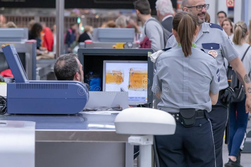 Airport, palma, mallorca, spain, 2019 april 14: Man in uniform standing at counter at checking point and watching at monitor with stock photos
