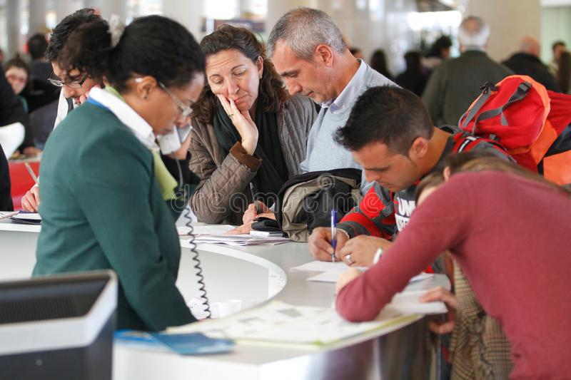 Airport passengers filling claims during a major flights delay. Passengers fill claims on an airline counter due to delays during a major strike day in palma de royalty free stock image