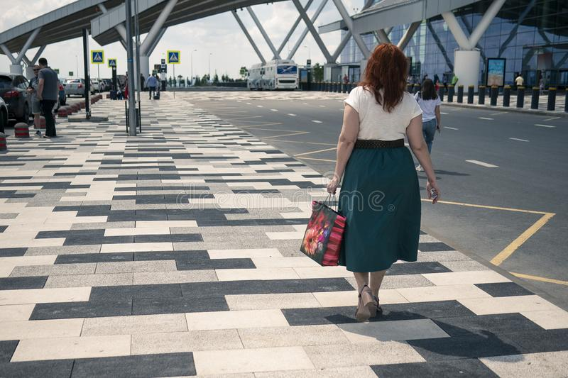 Airport Platov, Russia - 24.05.19: beautiful adult woman with red hair goes with the family to the airport. stock photography