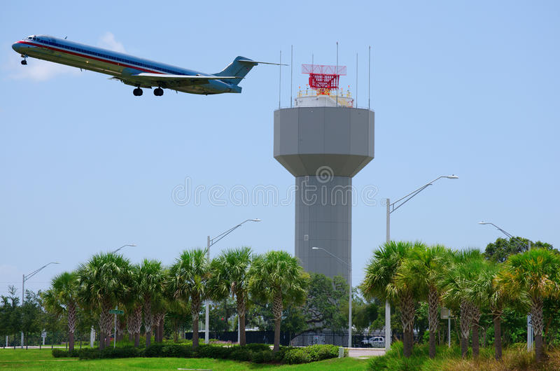 Airport radar with plane taking off. Airport radar with a plane taking off in the background in a tropical environment with palm trees in the foreground royalty free stock photography