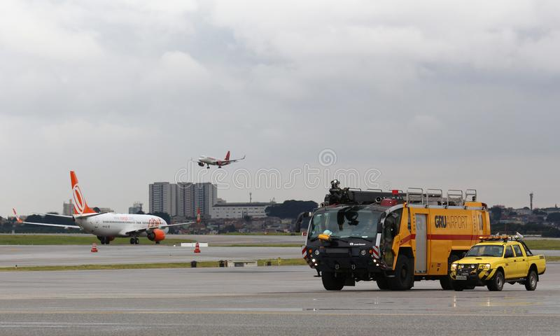 Airport ramp scene with emergency vehicles. An Airbus landing, a Boeing taxing, two airport emergency vehicles at Guarulhos International on a cloudy day stock photo