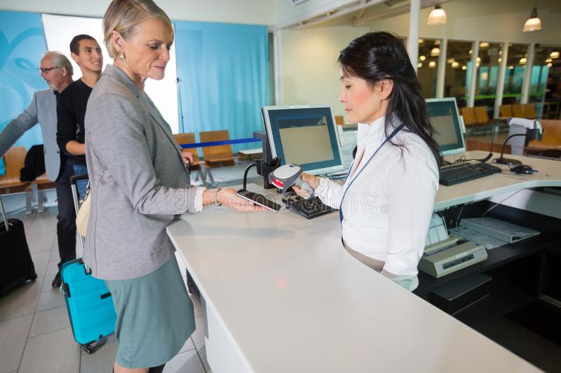 Airport Receptionist Scanning Barcode On Smart Phone Held By Bus. Mid adult receptionist scanning barcode on smart phone held by businesswoman at counter in royalty free stock photography