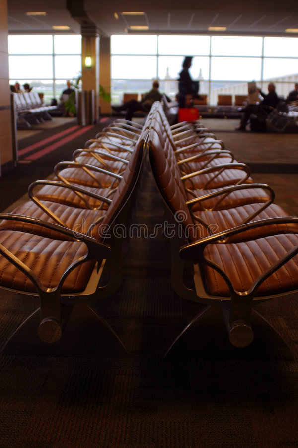 Airport seating with travelers in background royalty free stock images