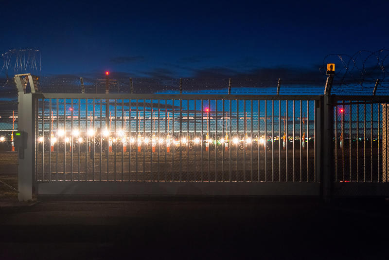 Airport security at dusk. Security fence around airport with runway lights in the background at dusk stock photos