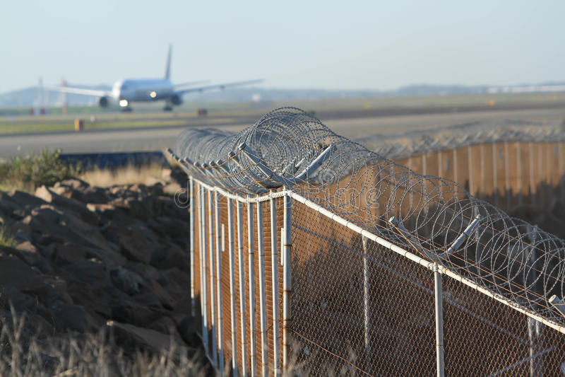 Airport security fence around runway. Airport security fence with jet airliner in background royalty free stock image