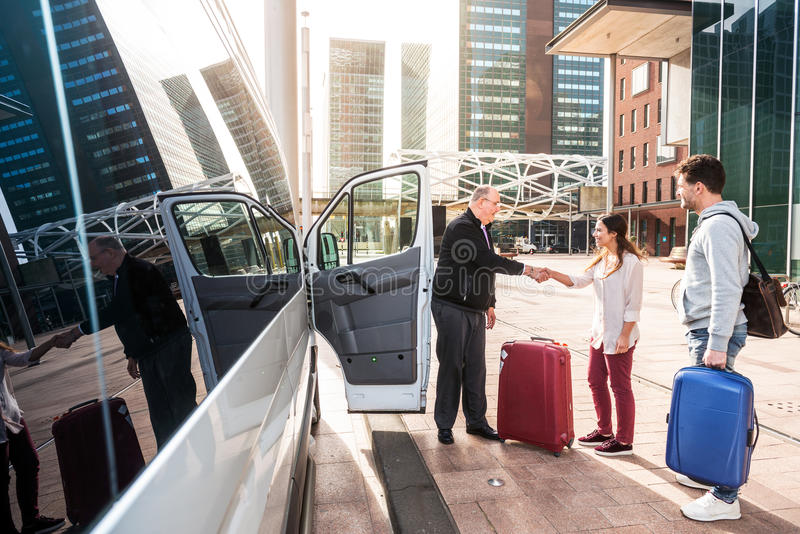 Airport Shuttle driver and passengers in a big city. Driver of a airport shuttle minivan, greeting his passengers with their luggage on the sidewalk of a modern royalty free stock photography