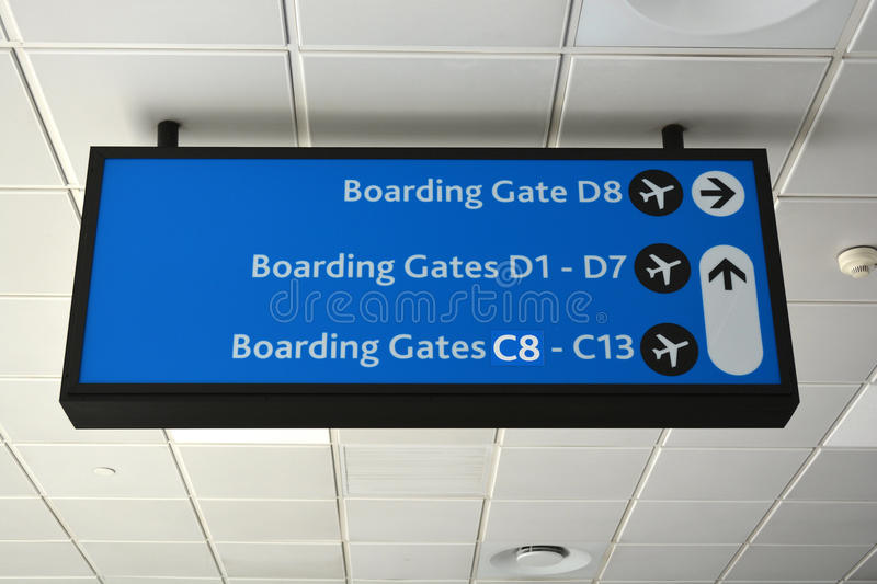 Airport sign for boarding gates. A big illuminated black and blue airport sign showing direction to the different boarding gates at the airport royalty free stock photos