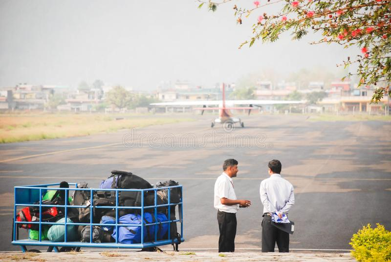Airport staff preparing baggages to loading into small passenger airplane stock images