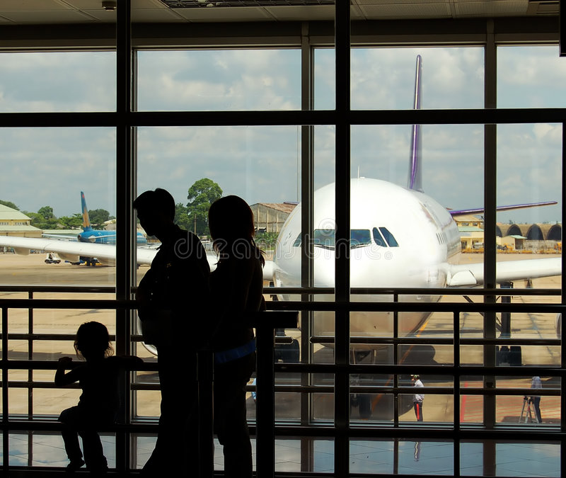 Airport terminal. A family at an airport terminal with aeroplane in the background