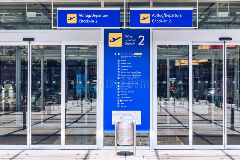 Airport terminal building gate entrance and automatic glass door with info text in german and english. Modern airport glass wall stock image