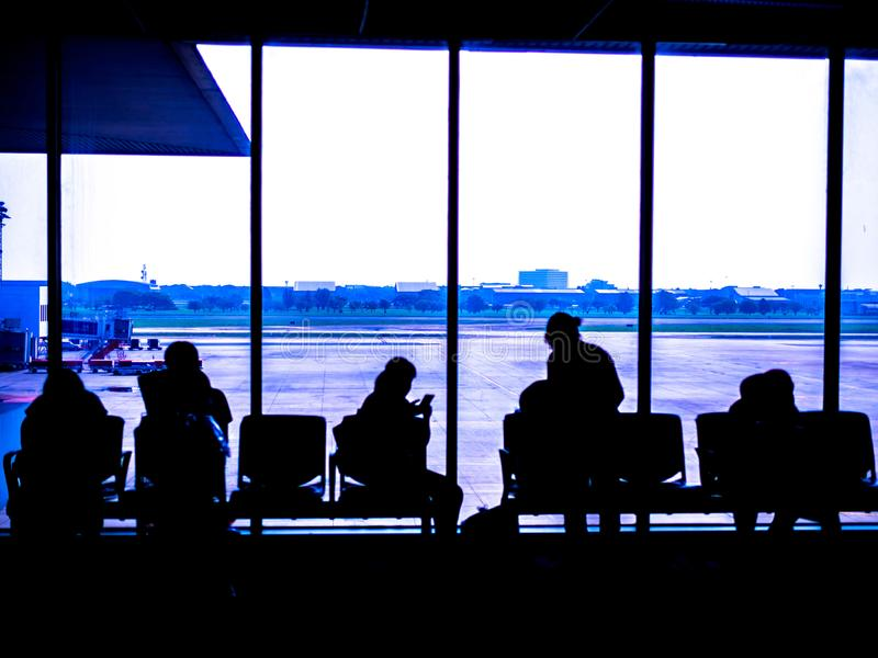 Airport terminal , Silhouettes of business people traveling on airport; waiting at the plane boarding gates.  royalty free stock photos
