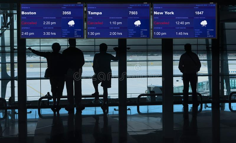 Airport terminal waiting on cancelled flights. People in an airport terminal waiting for thunder storm to end royalty free stock photography