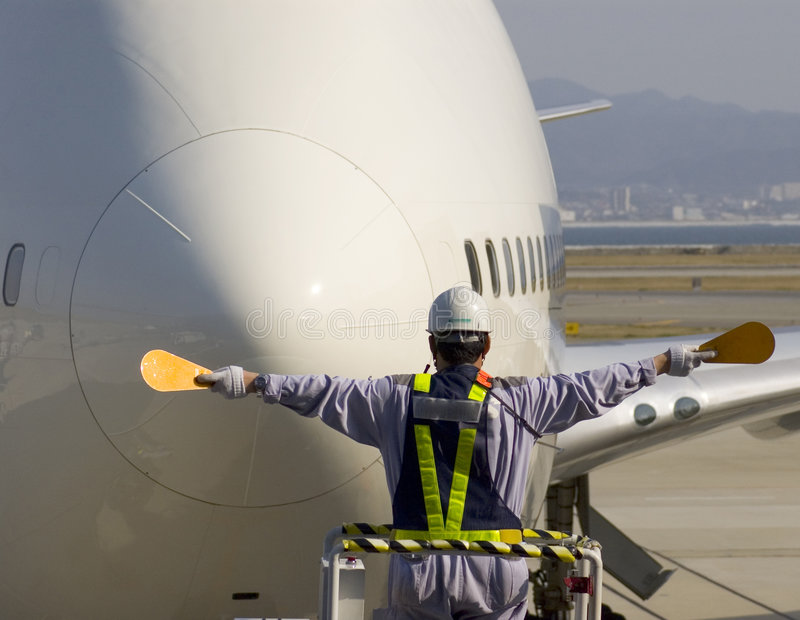 Airport Traffic Control. Airport Runway Controller with paddles guiding a very large jet plane into the boarding gate royalty free stock photos