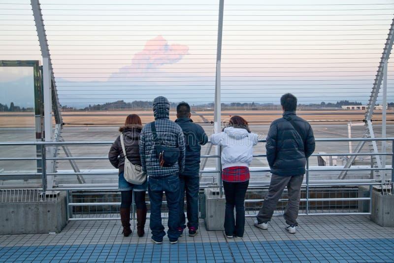 Airport visitors watch Shinmoedake volcano erupt. Kagoshima, Japan, February 3, 2011. People on airport viewing deck watch Shinmoedake volcano erupt. This stock images