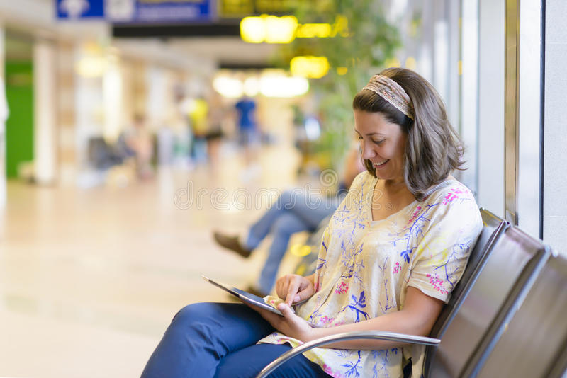 Airport Waiting Area. Young woman using a digital tablet in airport waiting area stock photo